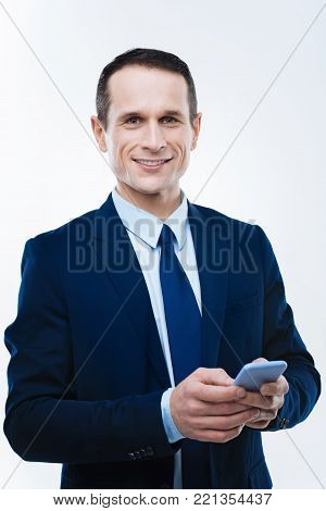 Modern gadget. Smart intelligent nice businessman holding his smartphone and looking at you while using it