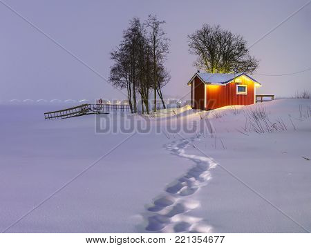 Evening snow-covered landscape with little scandinavian house.