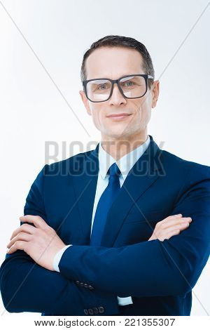 Confident businessman. Nice smart confident man smiling and standing cross handed while looking at you