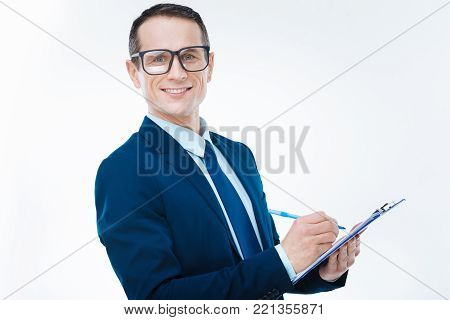 Corporate leader. Happy pleasant nice man smiling and taking notes while working for a serious corporation