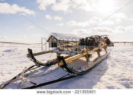 small unkempt sleighs against the backdrop of a hunting house