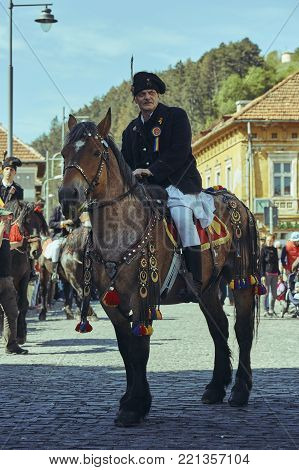 Brasov, Romania - April 27, 2014: Horseman rides thoroughbred stallion adorned with traditional decorations during the Junii Brasovului Festival.