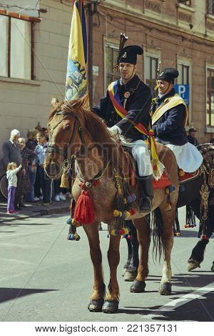 Brasov, Romania - April 27, 2014: Horseman rides chestnut horse adorned with traditional decorations and holds a flag during the Youths of Brasov (Junii Brasovului) Parade.