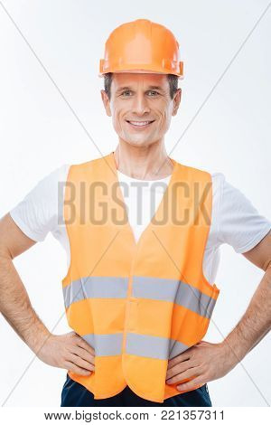 Favourite occupation. Nice handsome pleasant engineer smiling and looking at you while being ready to work