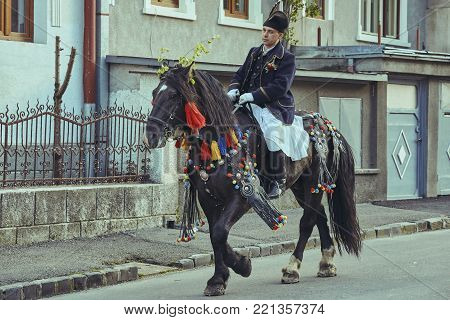 Brasov, Romania - April 27, 2014: Horseman rides thoroughbred stallion adorned with traditional decorations during the Youths of Brasov (Junii Brasovului) Parade.