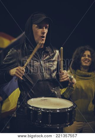 Bucharest, Romania - October 6, 2013: A protester loudly plays the drum during the population uprising against the cyanide open-cast gold extraction in Rosia Montana heritage site, Alba County.