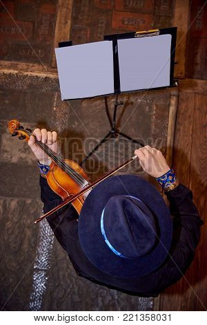 Fiddler in a hat playing the violin, top view