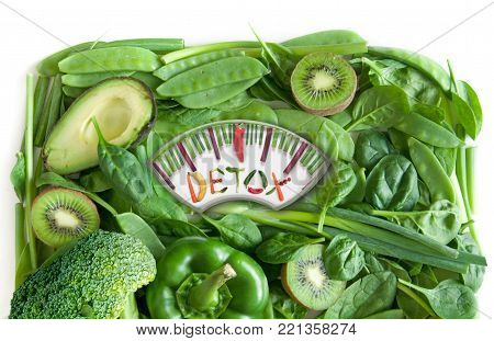 Green fruits and vegetables in the shape of bathroom weighing scales over a white background
