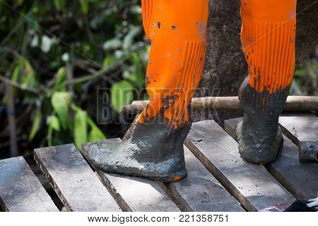 Orange rain boots on the legs of a man  after he played in the mud and got them dirty and muddy.