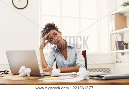 Deadline stress concept - sad african-american business woman sitting at desktop in office and holding hand on head. Hard working day.