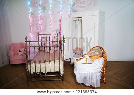 Children's room with a white wardrobe, woven metal bed. Cradle for newborns in a beautiful interior.