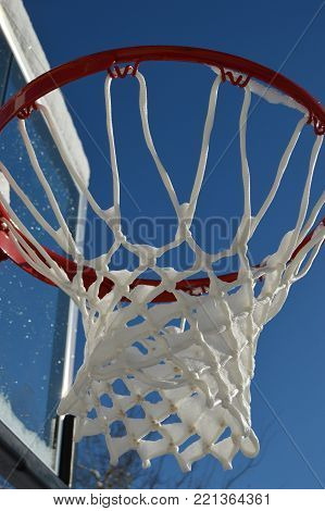 snow covered basketball net and backboard against sky
