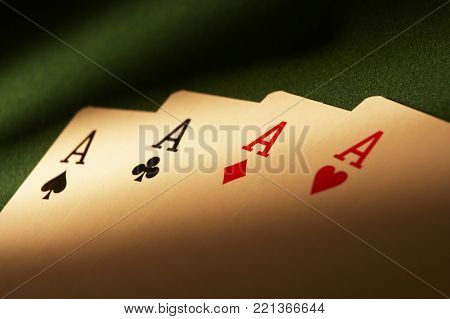 CLECKHEATON, WEST YORKSHIRE, UK: HAND OF PLAYING CARDS WITH FOUR ACES ON GREEN CLOTH GAMING TABLE, CIRCA 2007, CLECKHEATON, WEST YORKSHIRE, UK