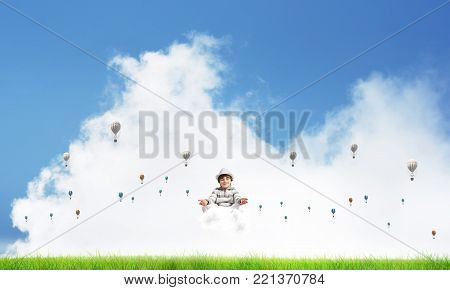 Young little boy keeping eyes closed and looking concentrated while meditating on cloud among flying aerostats with bright and beautiful landscape on background.