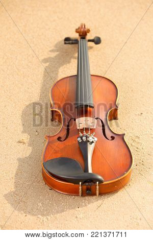 Violin on sandy beach. Love of music concept