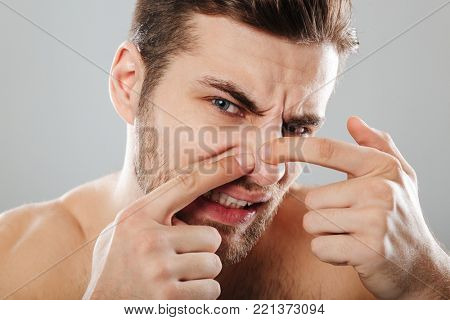 Close up portrait of a man squeezing pimple on his nose isolated over gray background