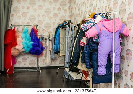 Close up different colorful clothes hanging on racks in changing room