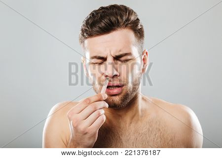 Man in pain removing nose hair with tweezers isolated over gray background