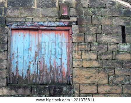 boarded window with decaying blue painted shutters with rotting wood in a derelict abandoned house with stone walls