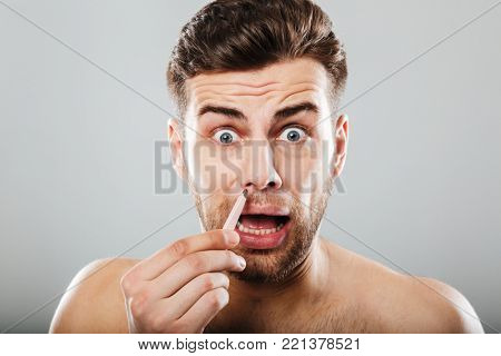 Scared man removing nose hair with tweezers isolated over gray background