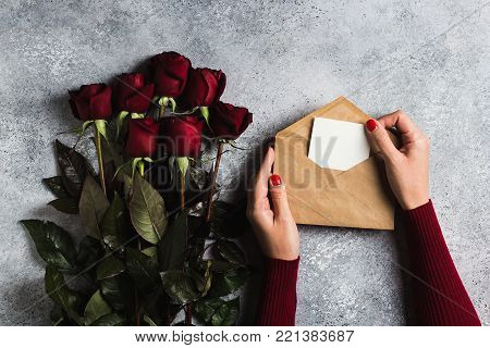Valentines day woman hand holding envelope love letter with greeting card mothers day red rose gift surprise on grey background with copyspace. Love flower gift for woman romantic holiday birthday