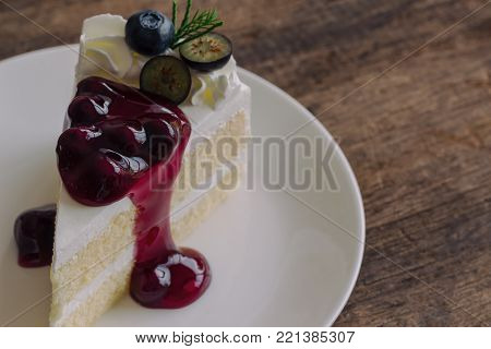 Blueberry cream cake on white plate on wood table in close up view. Vanilla blueberry sponge cake decorated with dairy whipped cream and blueberry sauce so soft sweet and delicious. Homemade bakery background. Blueberry cake ready to serve.