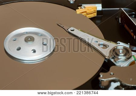 Close up inside of computer disk drive HDD . Detail of writing and reading head on acuator arm and axis, spindle and platters