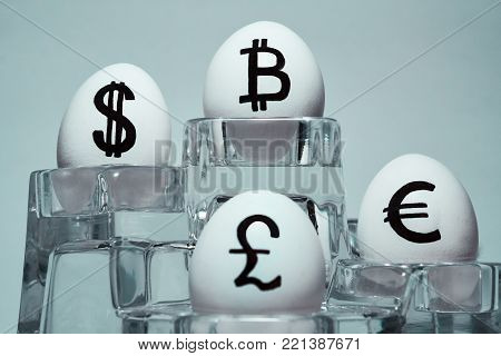 An inscription on chicken eggs for advertising and propaganda of various currencies of the world. Written or drawn symbols British pound sterling. dollar. Euro. Bitcoin.