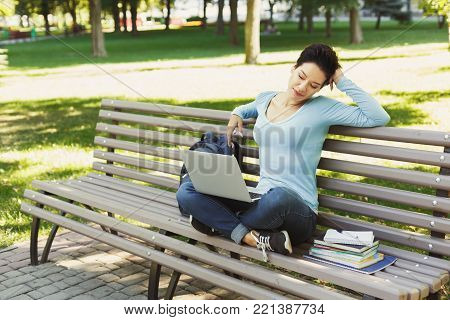 Young relaxed woman sitting outdoors on bench with laptop, surfing internet, preparing for exams. Technology, communication, education and remote working concept, copy space