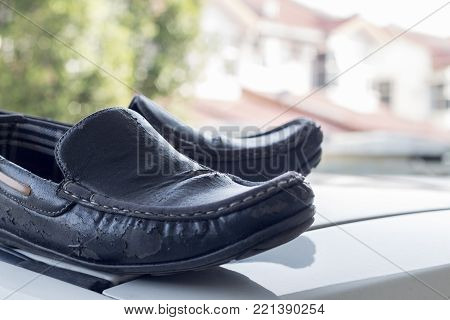 Black, well-worn men shoes with defocused background.