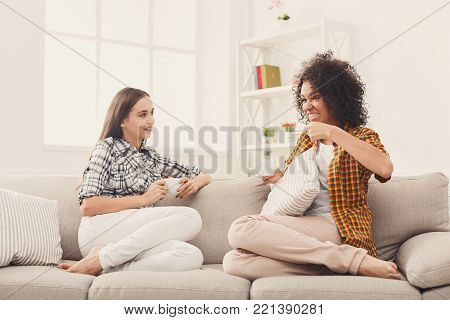 Two happy young female friends with coffee cups talking in living room at home, chatting about their life and relations, gossip and slumber party concept, copy space