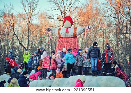 TULA, RUSSIA - MARCH 3, 2016: Traditional Maslenitsa Scarecrow on seeing Russian winter on last day of Shrovetide. Viewers awaiting initiation of ignition. Group of children standing at scarecrows