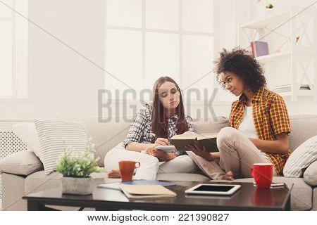 Two female friends enjoying weekend, laughing and having fun, reading books at home. Leisure, hobby, self-education concept, copy space