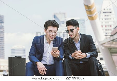 Asian business people use and play with their smart phone.