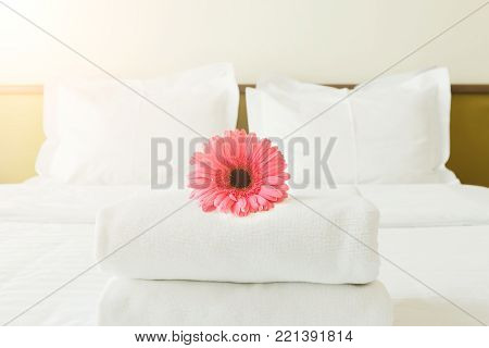 Stack of towels and flower on bed in hotel room. Bright gerbera as welcome gesture, room service, accommodation concept, copy space