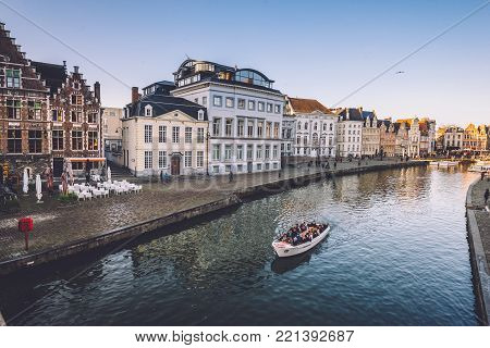 Ghent, Flanders, Belgium - December 27th, 2016. Medieval brick merchant houses and tourist cruise boat on Graslei and Korenlei street in Gent Old town. View from St. Michael bridge by winter morning.