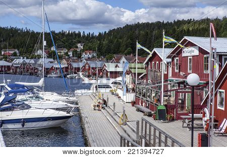 ULVON, SWEDEN ON JULY 18. View of the marina, lodges along the quay on July 18, 2017 in Ulvon, High Coast Heritage, Sweden. Boats and unidentified people. Editorial use.
