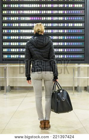 Casually dressed young female traveller checking a departures board at the airport terminal hall in front of check in couters. Flight schedule display blured in the background. Focus on woman.