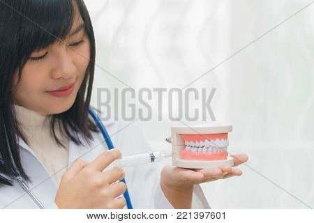 Female dentist demonstrate injecting local anaesthetic at gum with teeth model.