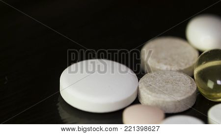 Pharmacy background on a dark table. Levitation pills. Tablets on a dark background which falling down. Pills. Medicine and healthy. Close up of capsules. Pills falling on black background.
