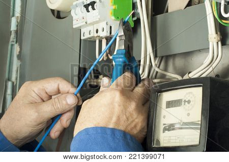 Worker man cutting electrical wires with pliers in fuse box. Electrical background.