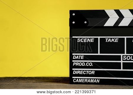 movie clapper on wood table with yellow background ; film, cinema and video photography concept