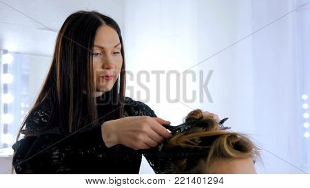 Professional hairdresser, stylist doing hairstyle for young pretty woman and using barrette for fixing hairdo in white make up room. Beauty and haircare concept