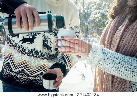 Young couple pours hot tea out of thermos in winter forest