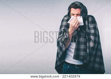 studio picture from a young man with handkerchief. Sick guy isolated has runny nose. man makes a cure for the common cold.Nerd is wearing glasses