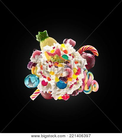 Milk shake with sweets and whipped cream, round form top view. Crazy freakshake food trend. Top view of whipped cream, full of berry and jelly sweets, chocolate candy. Colorful whipped cream concept. Monster shake, freak shake concept isolated
