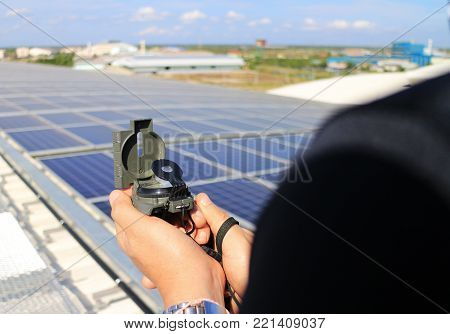 Hand Holding Compass at Solar Rooftop System Importance of Direction Concept