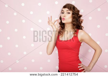 beautiful young curly woman in a red t-shirt on a pink background. copy spase