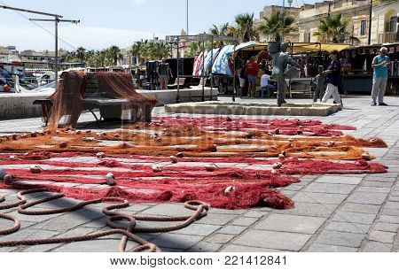 MARSAXLOKK, MALTA-NOVEMBER 23: drying nets in typical colorful maltese street on Nov 23, 2014. Daily life of maltese people in small Marsaxlokk village. Malta. Sunny winter day in Malta
