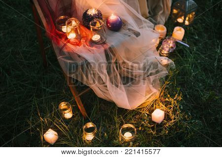 Night fine art outdoor wedding details: summer or spring ceremony with decor lowlight candles standing on chair covered with veil or soft tulle pastel tones and on the grass. Closeup view